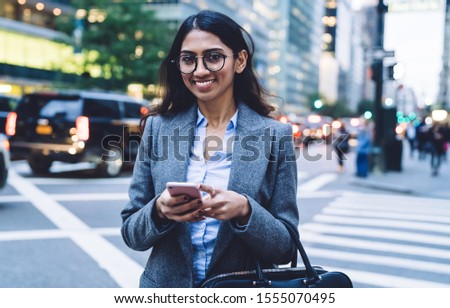 Young cheerful ethnic business woman using mobile phone and looking at camera while crossing road in New York City on daytime #1555070495