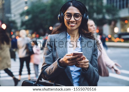 Glad young brunette ethnic woman in earphones spectacles gray coat and black handbag tapping on smartphone on busy New York street on urban blurred background and looking at camera #1555070516