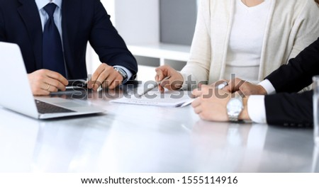 Business people discussing contract working together at meeting at the glass desk in modern office. Unknown businessman and woman with colleagues or lawyers at negotiation. Teamwork and partnership #1555114916