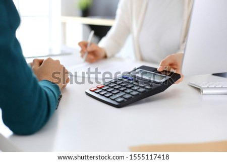 Accountant checking financial statement or counting by calculator income for tax form, hands close-up. Business woman sitting and working with colleague at the desk in office. Audit concept #1555117418