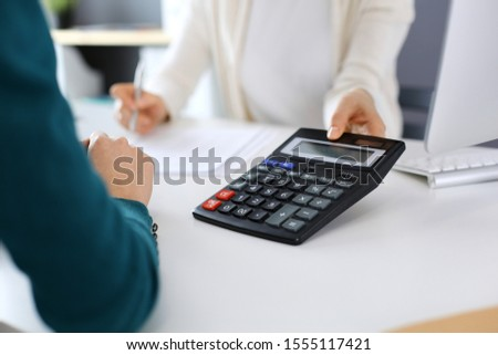 Accountant checking financial statement or counting by calculator income for tax form, hands close-up. Business woman sitting and working with colleague at the desk in office. Audit concept #1555117421