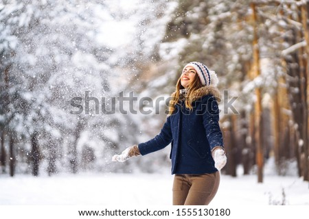 Happy young woman plays with a snow in sunny winter day. Girl enjoys winter, frosty day.  Playing with snow on winter holidays, a woman throws white, loose snow into the air. Walk in winter forest.