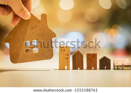 Hand choosing mini wood house model from model on wood table, selective focus, Planning to buy property. Choose what's the best. A symbol for construction ,ecology, loan concepts #1555188761