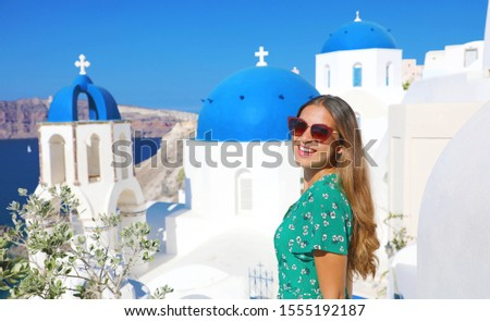 Happy tourist girl enjoying travel in Greece. Beautiful tanned woman with sunglasses visiting Oia village in Santorini island, Greece, Europe. #1555192187