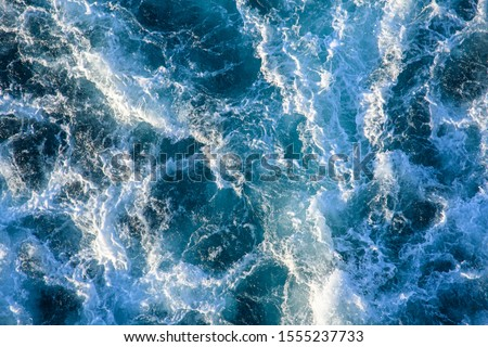 Seething waves with foam backlit by the setting sun. Transparent. Navy blue. Blue. Background. Pattern. Royalty-Free Stock Photo #1555237733