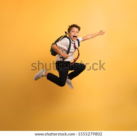 Young boy student jumps high like a super hero. Yellow background #1555279802