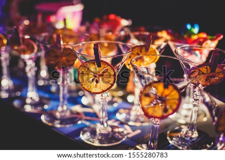 View of alcohol setting on catering banquet table, row line of different colored alcohol cocktails on a party, martini, vodka, and others on decorated catering bouquet table event #1555280783