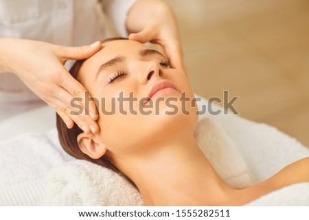 Beautiful woman has a facial massage in a beauty clinic. #1555282511