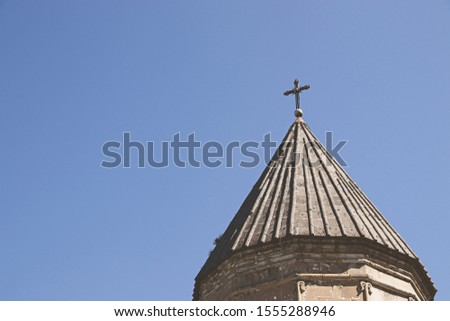 Christianity background image consisting of a cross on a church building with a blue sky background.