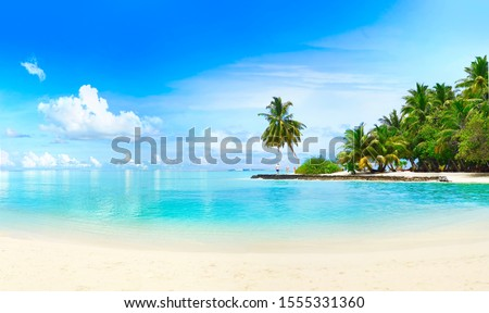 Beautiful beach with white sand, turquoise ocean, green palm trees and blue sky with clouds on Sunny day. Summer tropical landscape, panoramic view. Royalty-Free Stock Photo #1555331360