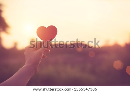 Silhouette broken heart,close up woman hand holding broken heart in the park. #1555347386