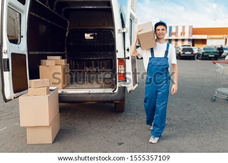 Deliveryman poses at the car with parcel boxes #1555357109