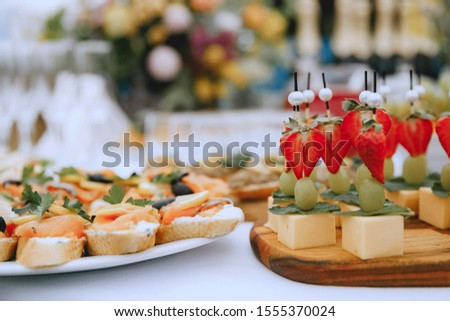 Buffet table. Appetizer of vegetables and fruits. Bright fruit and cheese plate. field service. Reception on the nature. Catering #1555370024