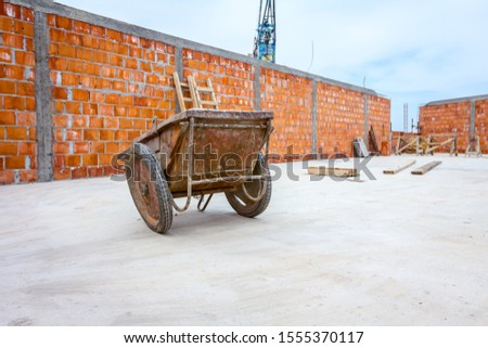 Industrial obsolete wheelbarrow is used for transportation burden at construction site. #1555370117