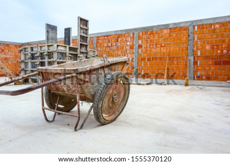 Industrial obsolete wheelbarrow is used for transportation burden at construction site. #1555370120