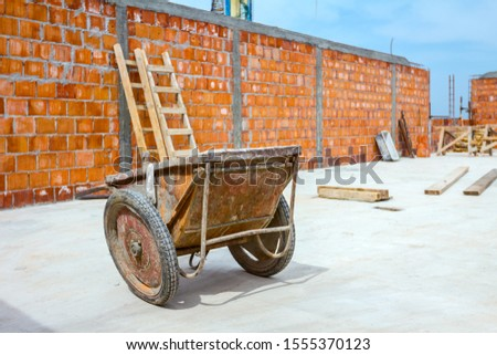 Industrial obsolete wheelbarrow is used for transportation burden at construction site. #1555370123