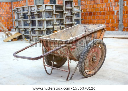 Industrial obsolete wheelbarrow is used for transportation burden at construction site. #1555370126