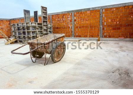 Industrial obsolete wheelbarrow is used for transportation burden at construction site. #1555370129