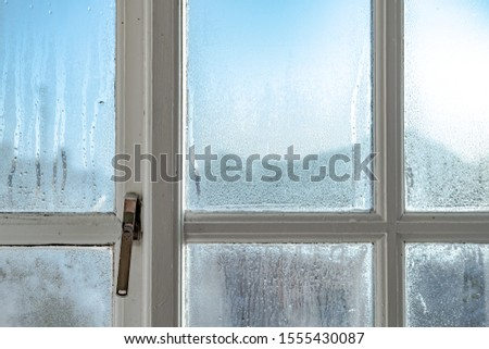 Cold room interior looking out onto water condensation formed on interior windows during early winter. Showing the wooden frame and metal lock, the condensation is known to cause damp and mould. Royalty-Free Stock Photo #1555430087