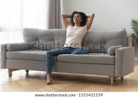 Satisfied African American woman with closed eyes relaxing on couch, happy calm girl with hand behind head resting on comfortable sofa at home, spending lazy weekend, daydreaming, stretching #1555431539