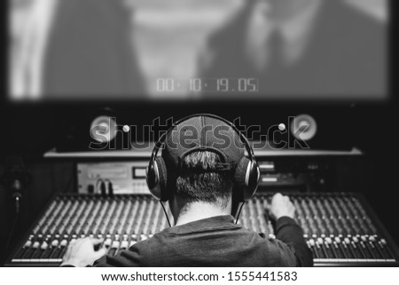 back of asian male professional producer, sound engineer, composer mixing audio track and music score on movie in sound studio. advertising, movie, drama post production concept