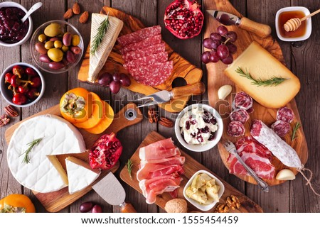Charcuterie boards of assorted cheeses, meats and appetizers. Above view table scene on a rustic wood background. #1555454459