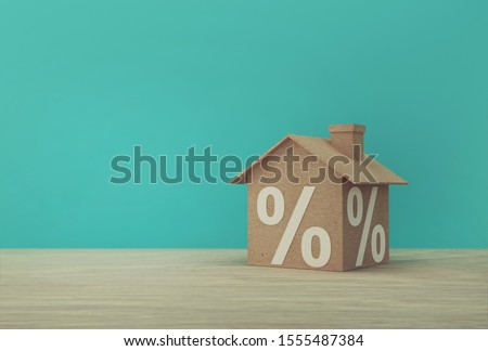 Creative idea of house model paper and percentage sign symbol icon  on wooden table. Property investment real estate and house mortgage financial concept. #1555487384