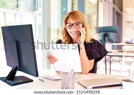 Portrait sho tof attractive mature businesswoman having a call and doing some paperwork while working in the office. #1555498298