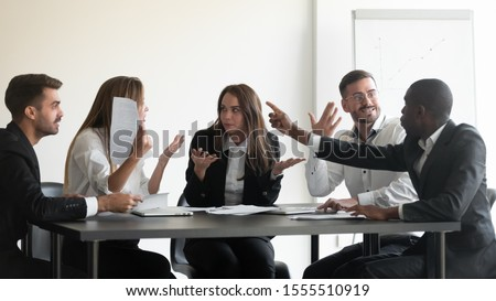 Mad frustrated multiethnic employees sit at office meeting dispute quarrel have stressful job situation, angry diverse colleagues debate fight over paperwork financial statistics, work stress concept #1555510919