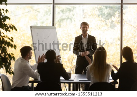 Excited multiethnic diverse employees listeners applaud thank smiling successful male speaker for presentation, happy multiracial colleagues clap hands greeting man presenter, acknowledgment concept #1555511213