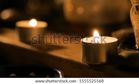 Tea light candles in the dark room. Warm romantic illumination, low key. Relaxation, meditative and chinese culture concept #1555525568