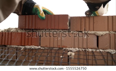 Worker builds a wall of red silicate brick.. Bricklayer build walls in accordance with construction plans #1555526750