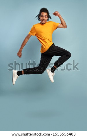 Full length overjoyed millennial African American man jumping high, happy lucky young guy having fun, looking at camera, celebrating victory, success, achievement, isolated on blue studio background. #1555556483