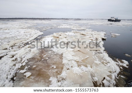 Autumn ice drift on the river. Ice floes on the river Northern Dvina. Arkhangelsk #1555573763