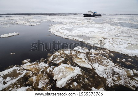 Autumn ice drift on the river. Ice floes on the river Northern Dvina. Arkhangelsk #1555573766