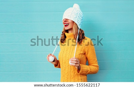 Winter portrait happy smiling young woman having fun pulls a hat over her eyes wearing yellow knitted sweater and white hat with pom pom on blue wall background #1555622117