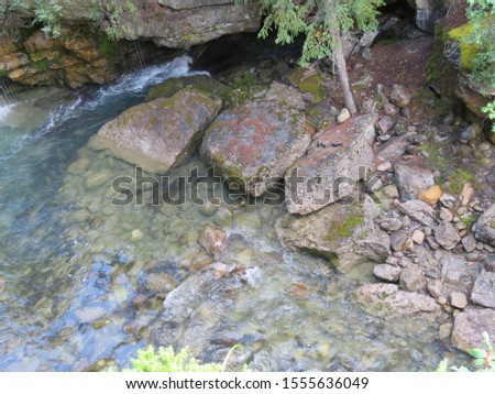 Transparent river water and shaped stones in Maligne Canyon. Beautiful clear river water from glaciers, interesting rocks, famous rocky valley in the Rocky Mountains of northern Canada. #1555636049