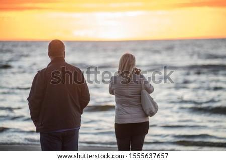 Jurmala, Latvia. Sunset at the Baltc sea. Man and woman at sunset Royalty-Free Stock Photo #1555637657