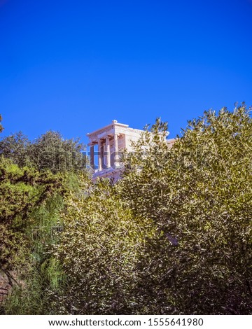 distant view of Athena Nike ancient temple between trees and clear blue sky, Athens Greece #1555641980