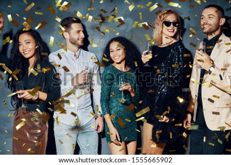 Happy young people dancing and having fun with confetti flying everywhere. Diverse group of people enjoy party. Holidays, celebration, nightlife and celebration concept       #1555665902