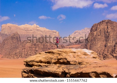 travel photography concept with posing young girl portrait on top of rock in Wadi Rum desert scenery landscape view environment Middle East Jordan