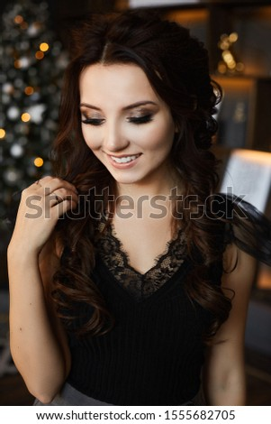 Portrait of a fashionable model girl with trendy hairstyle and trendy makeup in black blouse posing with festive lights of Christmas tree in background. Beautiful young woman with smooth perfect skin #1555682705