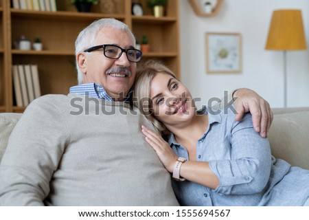 Pretty young smiling woman putting head on shoulder of her senior father embracing her while both watching tv at home #1555694567