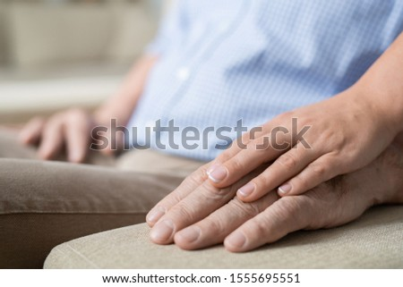 Hand of young affectionate and careful woman on that of her senior father on handle of beige soft couch #1555695551