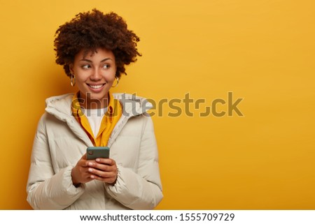Image of thoughtful young Afro American woman watches live stream online, enjoys pleasant messaging in chat, poses against yellow background in winter outerwear, looks on right side with smile #1555709729