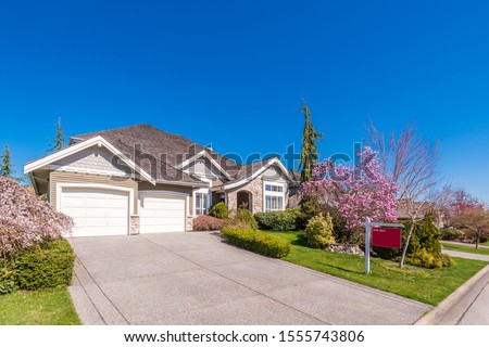 House for sale in Vancouver, Canada. Real estate sign in front of a house. #1555743806