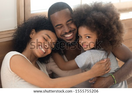 Happy african American young couple with preschooler sit hug posing looking at camera, loving biracial millennial parents with cute little daughter cuddle embrace enjoying tender moment at together #1555755206