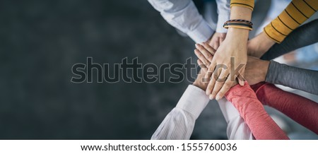 Close up top view of young business people putting their hands together. Stack of hands. Unity and teamwork concept. #1555760036