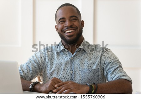 Headshot portrait of positive african American male in floral shirt sit at desk looking at camera laughing, happy millennial biracial man student or worker posing smiling making picture at workplace #1555760906