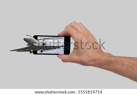 Hand holding a smart phone with the photo of a jet flying out of the screen.